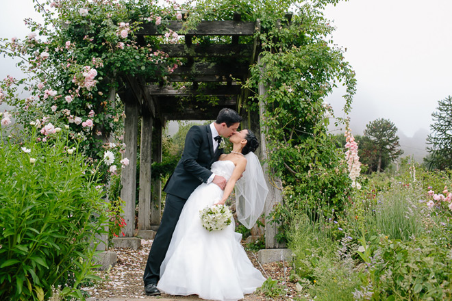 Bride and groom standing in rose arbor at their UC Berkeley Botanical Garden Wedding