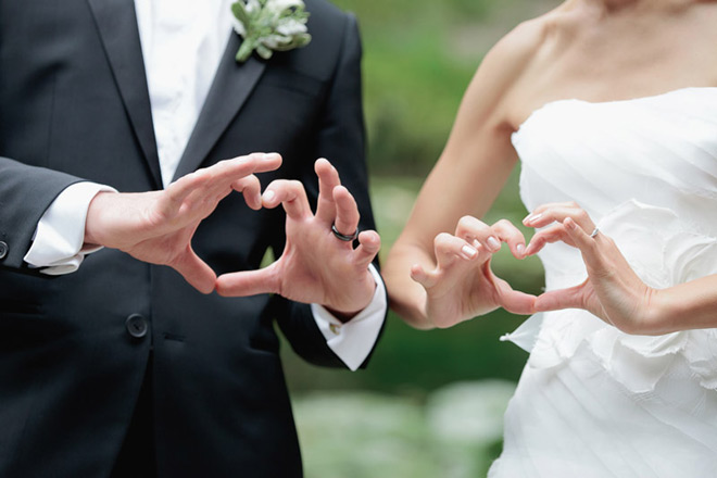 Bride and groom making love gesture with their hands