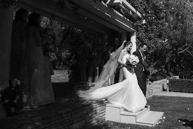 Carmel wedding photo of bride and groom standing under rose arbor
