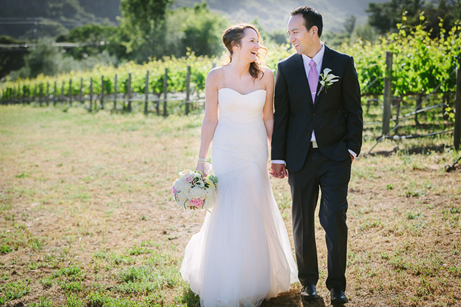 Bride and groom standing in vineyard in Carmel