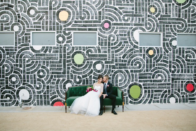 wedding couple sitting on sofa in front of a mural at the Ace Hotel in Palm Springs
