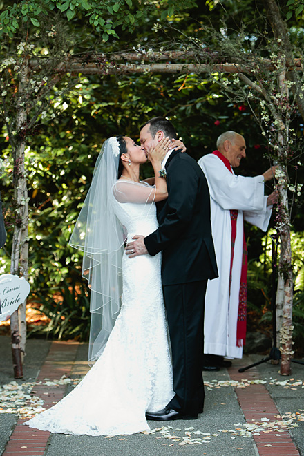 Bride and groom share kiss during their wedding ceremony at the Outdoor Art Club in Mill Valley