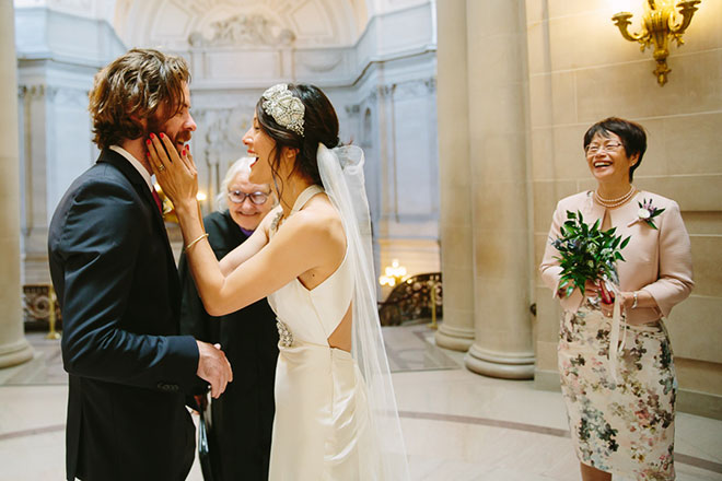 Bride and groom laughing during their San Francisco City Hall wedding ceremony