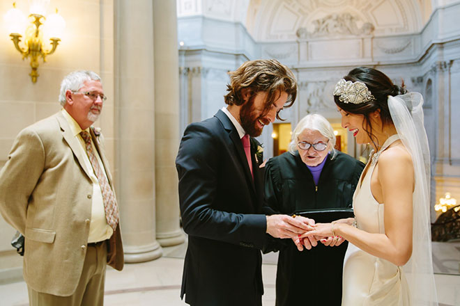 San Francisco City Hall wedding, Groom puts ring on bride's hand