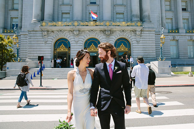 Bride and groom walking in front of San Francisco City Hall