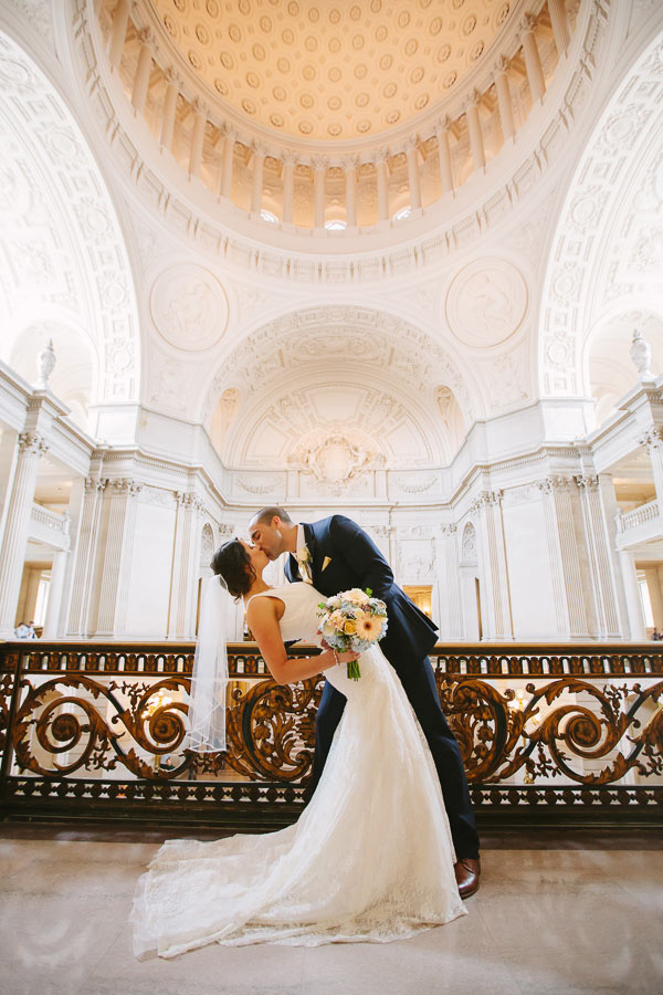 Bride and groom standing on Mayor's Balcony of San Francisco City Hall