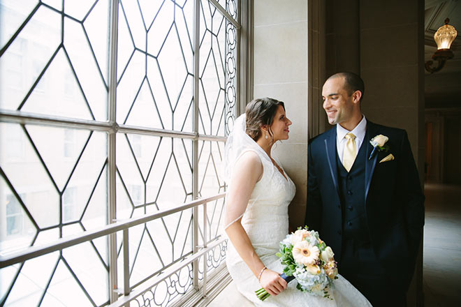 Bride and groom sitting on window sill of Third Floor of SF City Hall