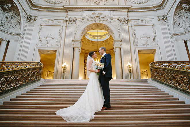 Just married couple standing on Grand Staircase of San Francisco City Hall