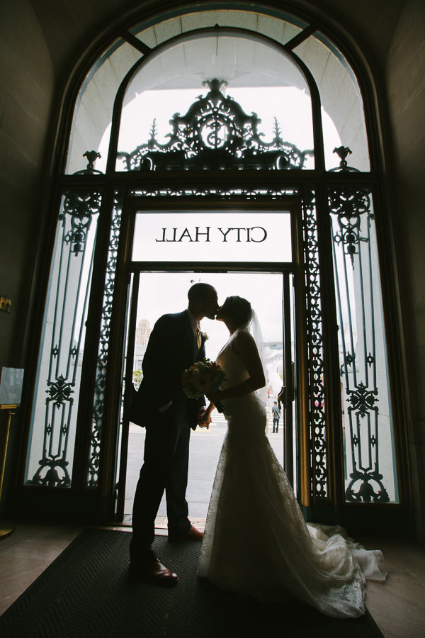 Silhouette photo of bride and groom standing in doorway of SF City Hall