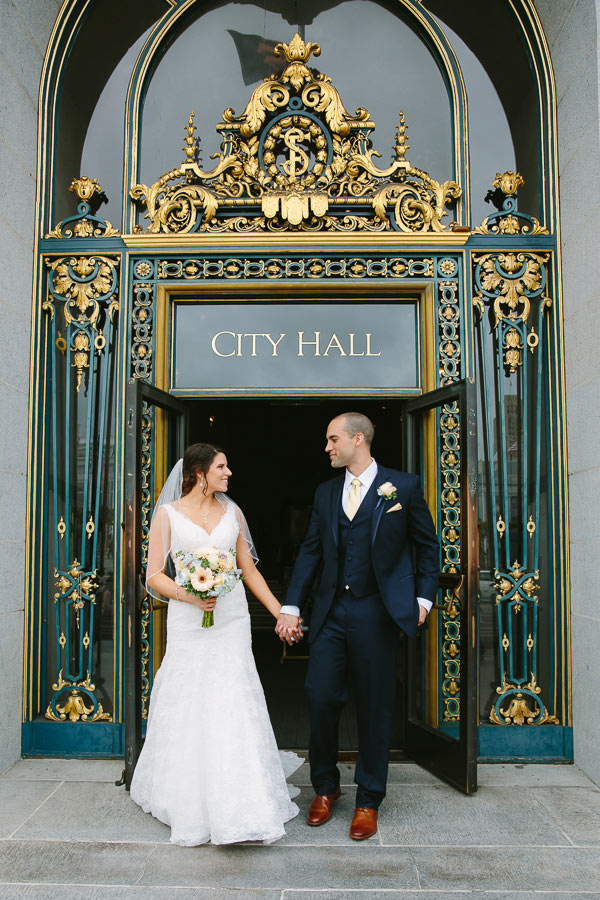 Bride and groom standing at front door of City Hall