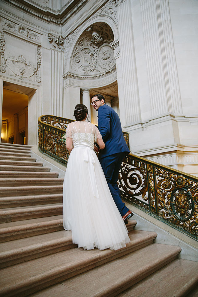 San Francisco wedding photographer, bride and groom walking on Grand Staircase inside City Hall