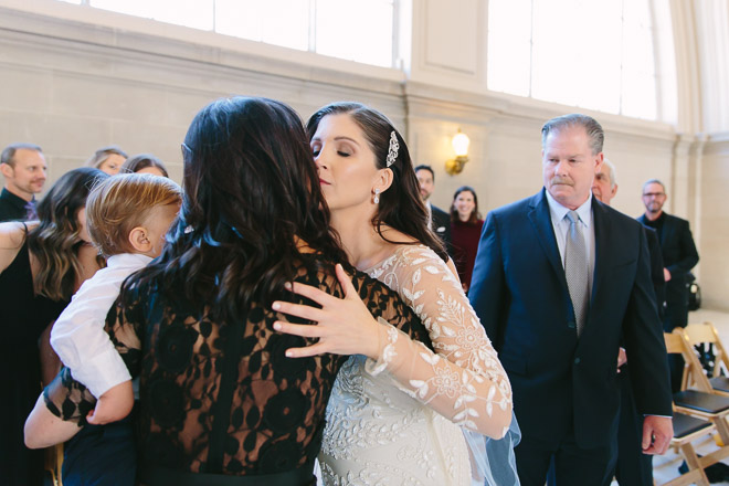 San Francisco wedding photographer, bride kisses her mother during wedding ceremony at San Francisco City Hall