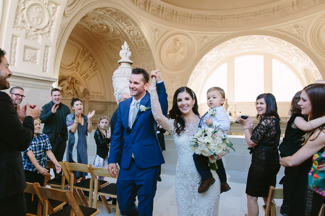 San Francisco wedding photographer, bride and groom and their son walk down the aisle together after their wedding ceremony at San Francisco City Hall