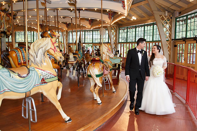 Bride and groom walking near the carousel at the San Francisco Zoo wedding