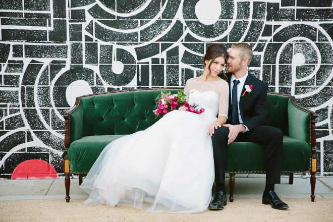 Bride and groom sitting on green sofa in front of mural at the Palm Springs Ace Hotel wedding photos