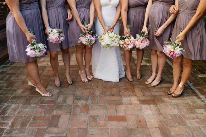 Bridesmaids in purple dresses holding their bouquets