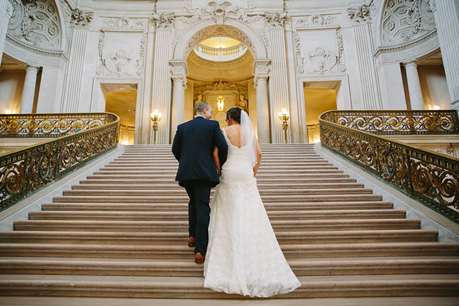 Bride and Groom walking up staircase at San Francisco City Hall