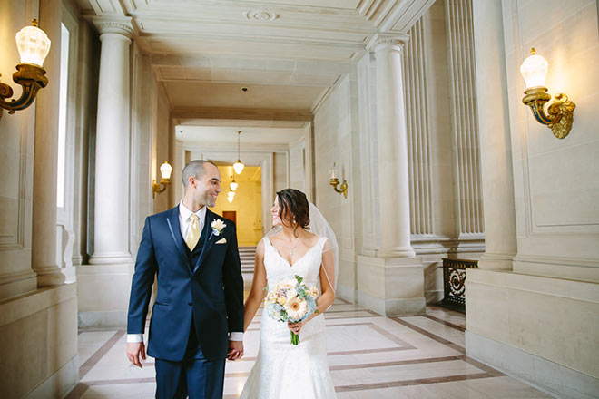 Bride and groom walking on second floor gallery of SF City Hall