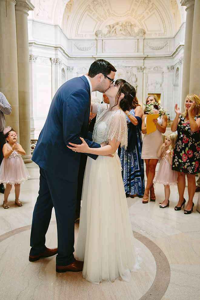 San Francisco wedding photographer, groom kisses his bride during their San Francisco City Hall wedding ceremony in the Rotunda