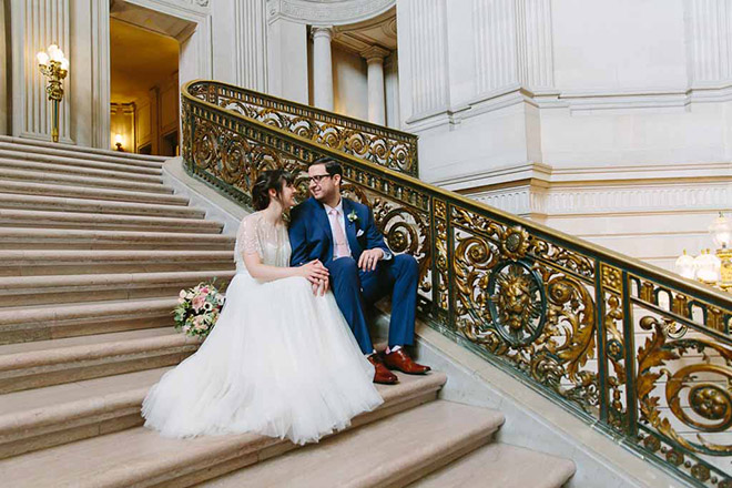 San Francisco wedding photographer, bride and groom sitting on Grand Staircase inside San Francisco City Hall