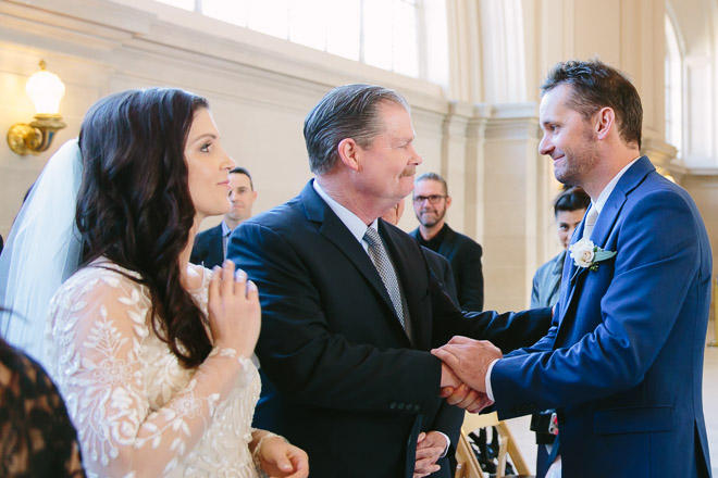 San Francisco wedding photographer, groom shakes the hand of the bride's father during the wedding ceremony at San Francisco City Hall