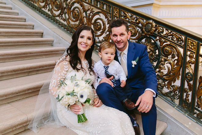 San Francisco wedding photographer, bride and groom with their son sitting on the Grand Staircase at San Francisco City Hall