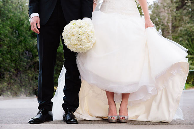 Closeup photo of groom's shoes and bride's white floral bouqet at the San Francisco Zoo wedding