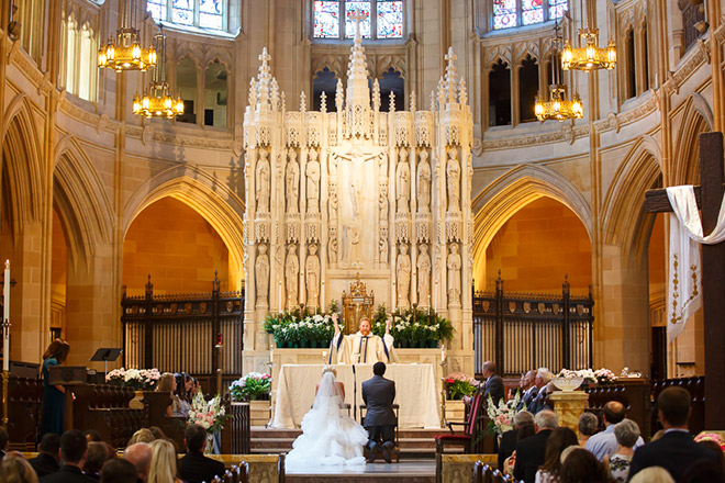 Bride and groom kneeling at altar of St Dominic Church in San Francisco